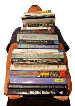 Estudante com pilha de livros