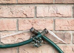 frozen outdoor green garden hose against brick house