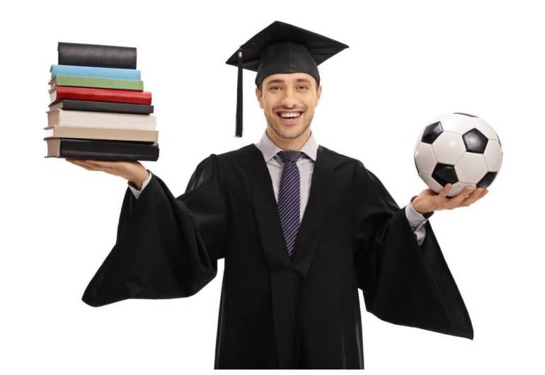A student athlete in a graduate's robe holds books in their left hand and a soccer ball in their right.