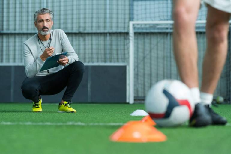 A Head Fitness  and Rehab Coach watches as a player dribbles a soccer ball between two cones.