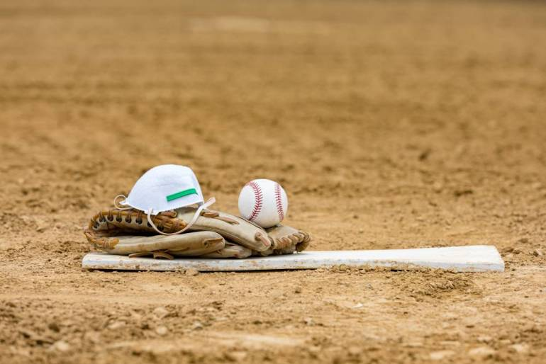 A baseball glove sits on a pitchers mound with a face mask and baseball.