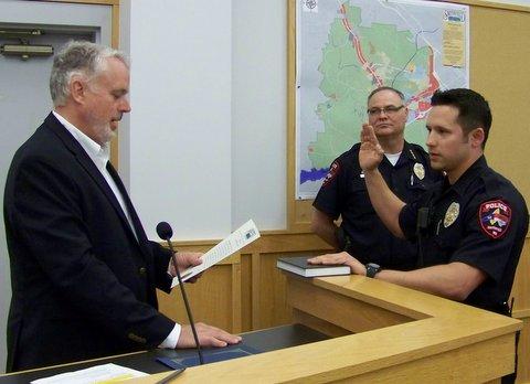 Officer Gabriel Galindo is sworn in by Smithfield Mayor John Lampe as Police Chief Michael Scott looks on. WTSB Photo