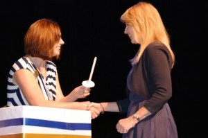 Catherine Page of Princeton receives her candle from advisor Stephanie Hall after signing the ceremonial guest book during the induction.