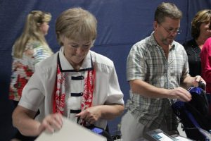 Board of Education member Peggy Smith (left) and David Prendergast from West Johnston High fill book bags with school supplies for students.