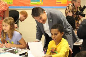NC Governor Pat McCrory (center) engages with Riverwood Middle School student Markel Judge (right). Seated beside them is student Carolina Holland.