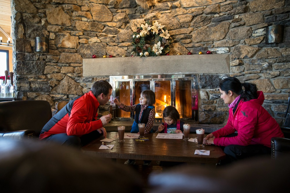 family in front of stone fireplace