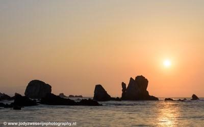 De lucht kleurt oranje bij zonsondergang op Playa Silencio.