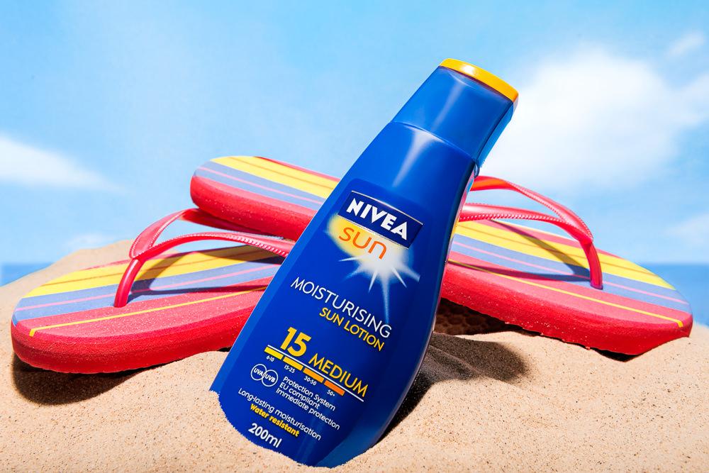 Sun lotion and flip flops on a beach