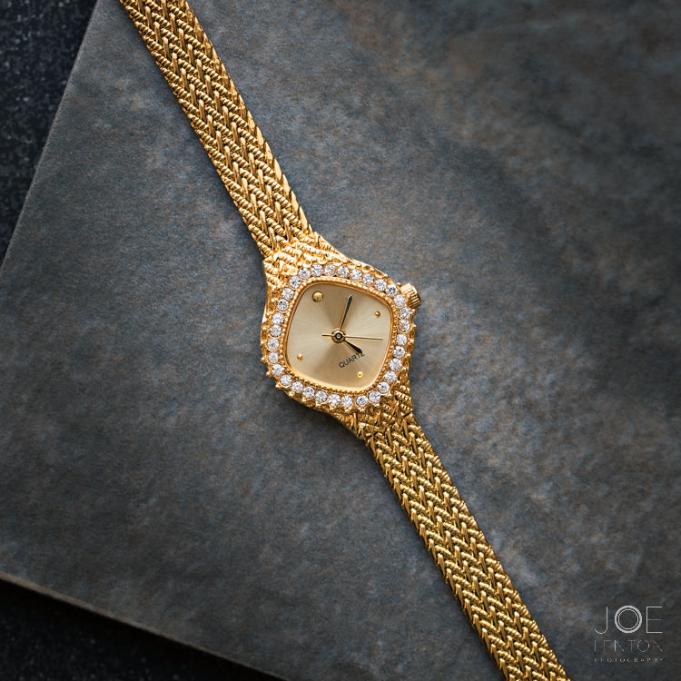 Gold watch laid flat on a tile