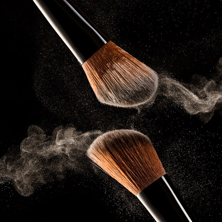 Makeup brushes with face powder in the air on black background