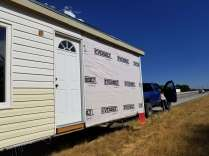 Picture showing the siding from the passenger side of the tiny house missing; additional siding from the front was also missing (not pictured).