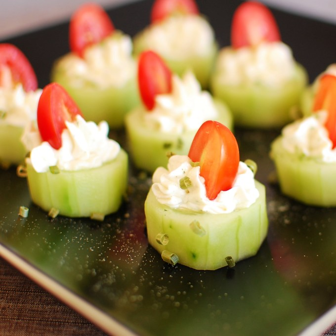 cucumber slices with piped on cream cheese and a halved grape tomato