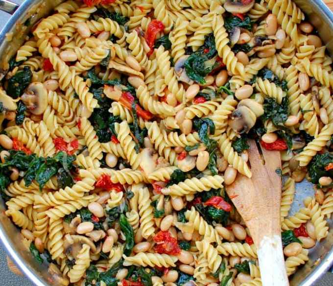 skillet of rotini pasta with mushrooms and wilted spinach ready to eat