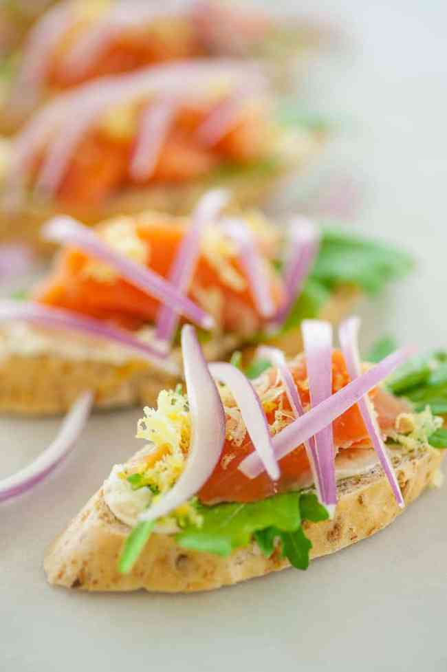 This is a smoked salmon appetizer with flavored cream cheese, arugula, lemon zest, and topped with sliced red onion. Only 82 calories for each. | joeshealthymeals.com