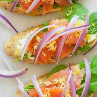 Smoked salmon appetizer with flavored cream cheese, arugula, lemon zest, and topped with sliced red onion. Only 82 calories for each. | joeshealthymeals.com