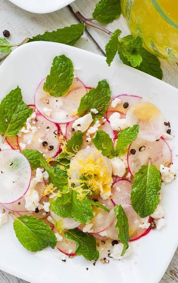 Shaved radish salad with feta, mint leaves, crushed peppercorns, and sea salt