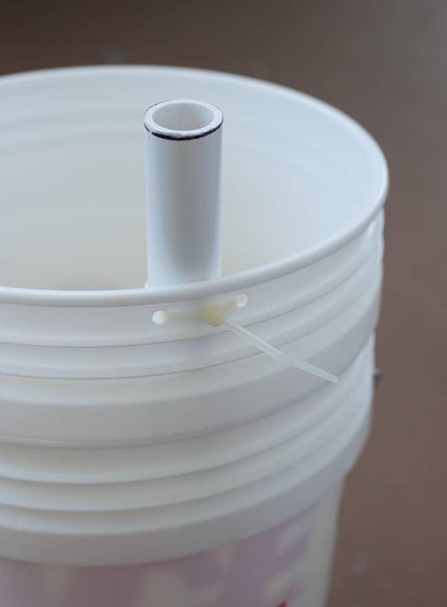 Zip tie the pipe to the bucket.