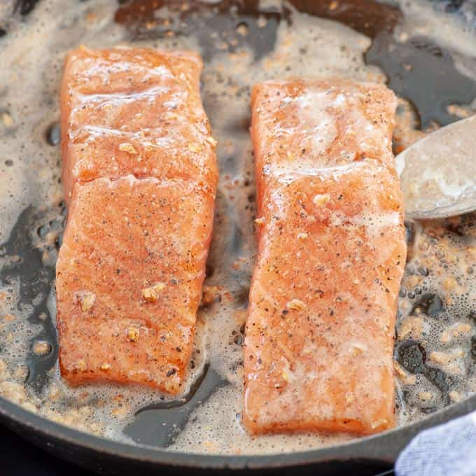 Salmon filets being basted in the skillet.