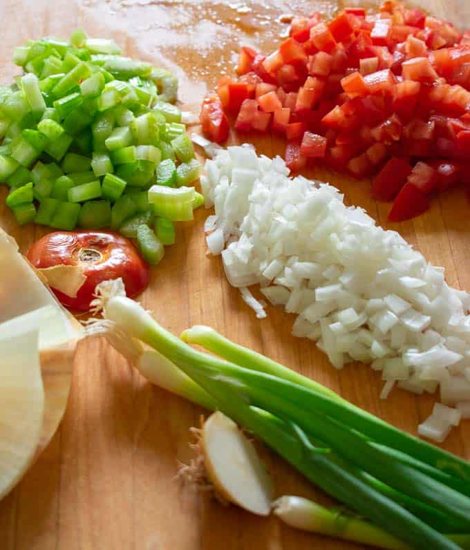 Chopped onions, celery and tomatoes for cold tuna salad.