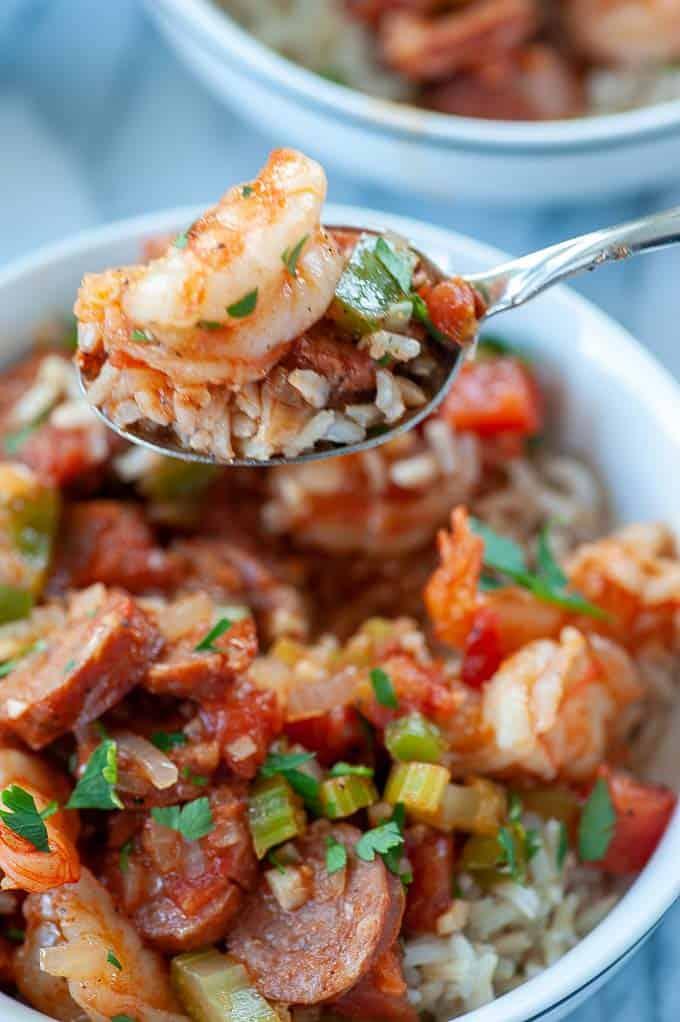 Close-up of a spoonful of jambalaya with sausage and shrimp.