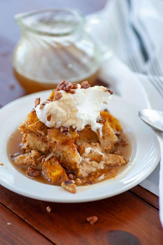 Pumpkin bread pudding with whipped cream, on a white plate.