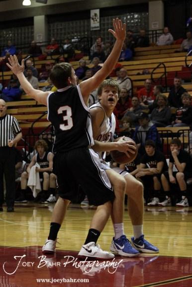 Otis-Bison Cougar Dylan Wissman (#11) makes a strong move towards the basket against Ellsworth Bearcat Shane Wilson (#3) at the 2012 Hoisington Winter Jam Basketball Tournament.