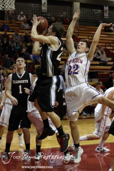 Ellsworth Bearcat Ben Murrell (#23) slips by Patrick Piper (#22) of the Otis-Bison Cougars during the 2012 Hoisington Winter Jam Basketball Tournament.