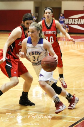 Tori Ptacek (#31) of the Russell Lady Broncos drives past Hoisington Lady Cardinals Mallory Flagor (#32) and Jordin Greer (#10) at the 2012 Hoisington Winter Jam Basketball Tournament.
