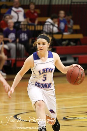 Alex Ptacek (#5) of the Russell Lady Broncos dribbles the basketball against the Hoisington Lady Cardinals at the 2012 Hoisington Winter Jam Basketball Tournament.