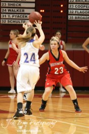 Hoisington Lady Cardinal Blakelee Cooper (#23) defends against Russell Lady Bronco Kaitlyn Walker (#24) at the 2012 Hoisington Winter Jam Basketball Tournament.