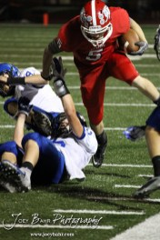 McPherson Bullpup Kyler Kinnamon (#5) hurdles two Winfield Vikings defenders during the Winfield at McPherson football game that ended in a 47 to 8 victory for the Bullpups at the McPherson Stadium in McPherson, Kansas on September 28, 2012. (Photo: Joey Bahr, www.joeybahr.com)