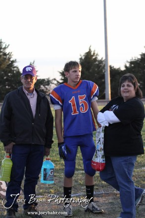 Otis-Bison Cougar Justus Bartonek (#15) stands with his parents before the Wilson High School at Otis-Bison High School Eight Man Division II District 7 matchup with Otis-Bison winning 60-14 in Otis, Kansas on October 19, 2012. (Photo: Joey Bahr, www.joeybahr.com)
