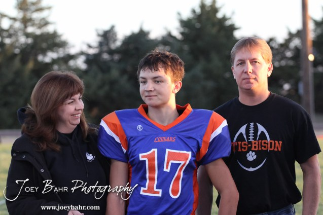 Otis-Bison Cougar Justin Jecha (#17) stands with his parents before the Wilson High School at Otis-Bison High School Eight Man Division II District 7 matchup with Otis-Bison winning 60-14 in Otis, Kansas on October 19, 2012. (Photo: Joey Bahr, www.joeybahr.com)