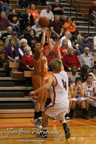 Kiowa County Maverick Caleb Davis (#4) shoots a three point shot while Larned Indian Grant Unruh (#4) defends during the Larned Indians versus Kiowa County Mavericks First Round Game with Kiowa County winning 63 to 45 at the 6th Annual Keady Basketball Classic held at Larned Middle School in Larned, Kansas on December 3, 2012. (Photo: Joey Bahr, www.joeybahr.com)