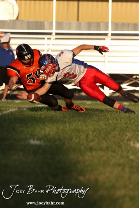 Ellinwood Eagle Kaleb Schartz (#3) and Larned Indian Roger Klenke (#56) scramble for a loose ball during the Ellinwood versus Larned High School football game with the Larned Indians winning 60 to 0 at Larned High School in Larned, Kansas on September 13, 2013. (Photo: Joey Bahr, www.joeybahr.com)