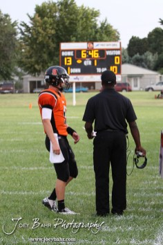 Larned Indian Head Coach AB Stokes talks to his quarterback, Easton Palmer (#9), during the Ellinwood versus Larned High School football game with the Larned Indians winning 60 to 0 at Larned High School in Larned, Kansas on September 13, 2013. (Photo: Joey Bahr, www.joeybahr.com)