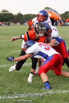 Ellinwood Eagles Gavin Vink (#35), Kaleb Schartz (#3), and Chance Baker (#34) tackle Larned Indian Brayden Smith (#3) during the Ellinwood versus Larned High School football game with the Larned Indians winning 60 to 0 at Larned High School in Larned, Kansas on September 13, 2013. (Photo: Joey Bahr, www.joeybahr.com)