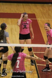 The Hoisington Lady Cardinals enjoy a quick laugh after scoring a point during the Hoisington versus Smoky Valley volleyball match with Hoisington winning in two sets at Hoisington Activity Center in Hoisington, Kansas on October 22, 2013. (Photo: Joey Bahr, www.joeybahr.com)