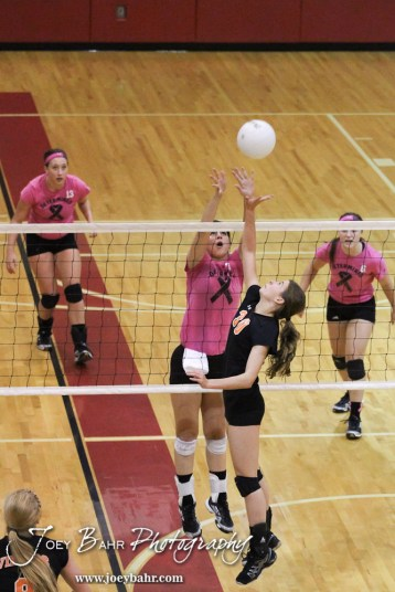 Smoky Valley Lady Viking Rilee Carson (#30) goes to hit the ball over while Hoisington Lady Cardinal Jordan Moore (#7) attempts to block it during the Hoisington versus Smoky Valley volleyball match with Hoisington winning in two sets at Hoisington Activity Center in Hoisington, Kansas on October 22, 2013. (Photo: Joey Bahr, www.joeybahr.com)