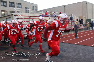 Hoisington Cardinal Seth Owen (#79) leads the team onto the field before the KSHSAA Class 4A District 15 Football game between Scott City and Hoisington with Scott City winning 14 to 0 at Elton Brown Field in Hoisington, Kansas on October 18, 2013. (Photo: Joey Bahr, www.joeybahr.com)