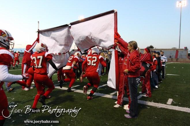 The Hoisington Cardinals run through a banner prior to the KSHSAA Class 4A District 15 Football game between Scott City and Hoisington with Scott City winning 14 to 0 at Elton Brown Field in Hoisington, Kansas on October 18, 2013. (Photo: Joey Bahr, www.joeybahr.com)