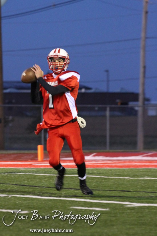 Hoisington Cardinal Taylor Richter (#7) prepares to throws a pass during the KSHSAA Class 4A District 15 Football game between Scott City and Hoisington with Scott City winning 14 to 0 at Elton Brown Field in Hoisington, Kansas on October 18, 2013. (Photo: Joey Bahr, www.joeybahr.com)