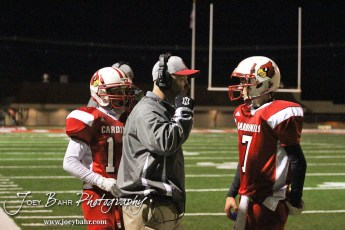 Hoisington Cardinal Head Coach Jason Ingram gives the next play to Quarterback Taylor Richter (#7) during the KSHSAA Class 4A District 15 Football game between Scott City and Hoisington with Scott City winning 14 to 0 at Elton Brown Field in Hoisington, Kansas on October 18, 2013. (Photo: Joey Bahr, www.joeybahr.com)