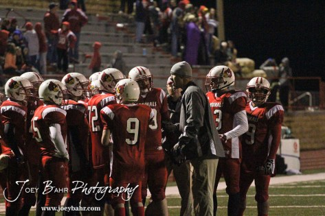 Hoisington Cardinal Assistant Coach Zach Baird addresses his players during a timeout during the KSHSAA Class 4A District 15 Football game between Scott City and Hoisington with Scott City winning 14 to 0 at Elton Brown Field in Hoisington, Kansas on October 18, 2013. (Photo: Joey Bahr, www.joeybahr.com)