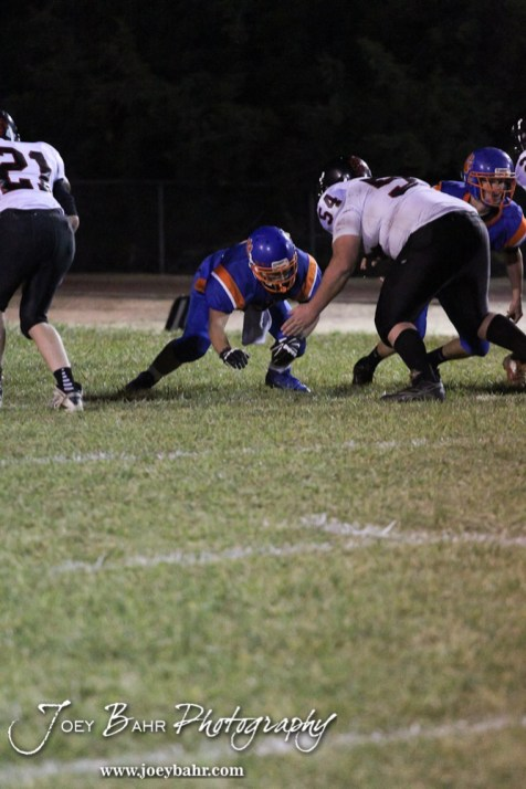Otis-Bison Cougar Kade Hagans (#23) goes to block Sylvan-Lucas Mustang Fritz Berger (#54) during the Sylvan-Lucas vs Otis-Bison High School football game with Otis-Bison winning 32 to 30 at Otis-Bison High School Field in Otis, Kansas on October 31, 2013. (Photo: Joey Bahr, www.joeybahr.com)