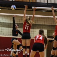 Larned Lady Indian Maci Perez (#3) hits the ball over the net as Kingman Lady Eagle Sada Smith (#11) tries to block during the Kingman Lady Eagles versus Larned Lady Indians volleyball match with Kingman winning 25-21, 24-26, 25-15 at Hoisington Activity Center in Hoisington, Kansas on September 9, 2014. (Photo: Joey Bahr, www.joeybahr.com)