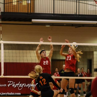 Kingman Lady Eagles Sydney Bangert (#22) and Michaela Theis (#23) try to set a wall during the Kingman Lady Eagles versus Larned Lady Indians volleyball match with Kingman winning 25-21, 24-26, 25-15 at Hoisington Activity Center in Hoisington, Kansas on September 9, 2014. (Photo: Joey Bahr, www.joeybahr.com)