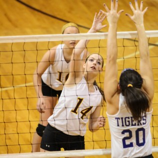 Victoria Lady Knight Brooke Pfanenstiel (#14) hits the ball over the net as St. John Lady Tiger Teresa Christie (#20) defends during the 2014 Central Prairie League Volleyball Tournament at Hoisington Activity Center in Hoisington, Kansas on October 18, 2014. (Photo: Joey Bahr, www.joeybahr.com)