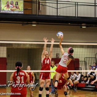 Macksville Lady Mustang Taylor Gillespie (#2) goes for a kill as Kinsley Lady Coyote Lydia Duft (#14) tries to block during the 2014 Central Prairie League Volleyball Tournament at Hoisington Activity Center in Hoisington, Kansas on October 18, 2014. (Photo: Joey Bahr, www.joeybahr.com)