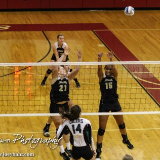 LaCrosse Lady Leopards Marissa Wagner (#21) and Morgan West (#15) try to block a shot from Central Plains Lady Oiler Taylor Rolfs (#14) during the 2014 Central Prairie League Volleyball Tournament at Hoisington Activity Center in Hoisington, Kansas on October 18, 2014. (Photo: Joey Bahr, www.joeybahr.com)